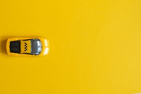 Toy taxi car on a yellow background with copy space Imagens