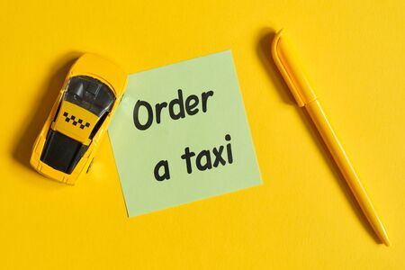 Taxi order concept with text on sticker and toy car on a yellow background