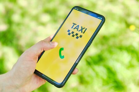 Concept of taxi call through the application on a smartphone holding a hand