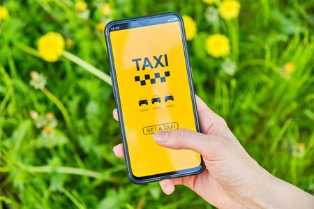 A hand holds a smartphone and selects a taxi through the application