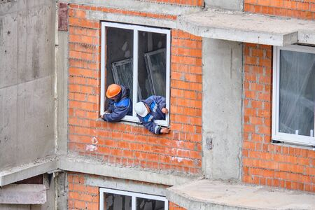 Workers at a construction site install windows in a residential building.