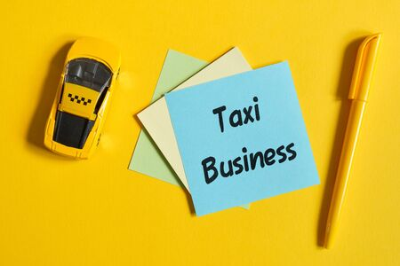 The concept of a taxi as a business. Toy car on a yellow background with a sticker. Top view Imagens