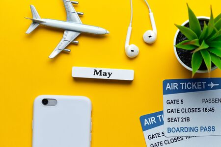 May vacation concept - toy airplane with tickets on yellow background
