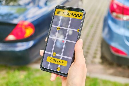 Hand holds smartphone and finger clicks on taxi search button in application Imagens