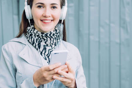 Caucasian girl in headphones smiling and looking at the camera while listening to music.