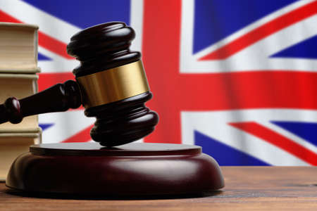 Justice and court concept in United Kingdom of Great Britain and Northern Ireland. Judge hammer on a flag background.