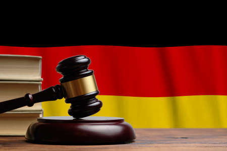 Justice and court concept in Federal Republic of Germany. Judge hammer on a flag background