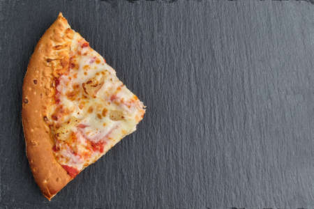 Hawaiian pizza slice on slate board with copy space and top view.