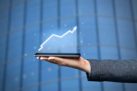 The concept of growth and business success. The hand holds the tablet with the graphics and the up arrow