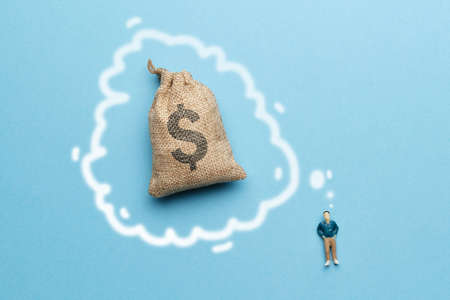 The concept of the dream of wealth. The figurine of a man next to a bag of money