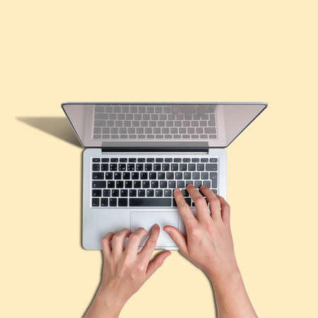 A person use a laptop against a yellow background Banque d'images