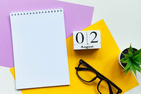 2nd august - second day month calendar concept on wooden blocks with copy space in notebook.