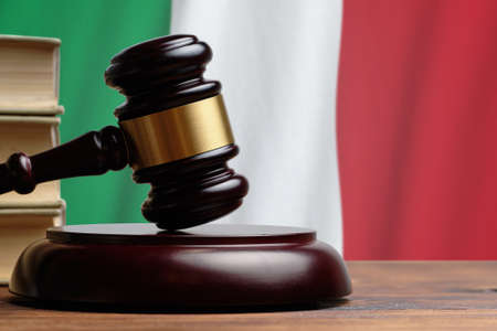 Justice and court concept in Italian Republic. Judge hammer on a Italy flag background. Banque d'images