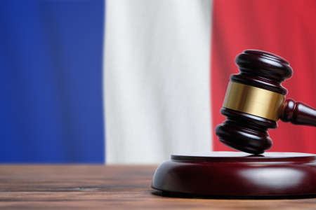 Justice and court concept in French Republic France. Judge hammer on a flag background.