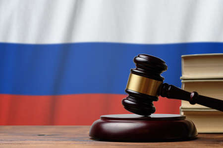 Justice and court concept in Russian Federation. Judge hammer on a flag background.