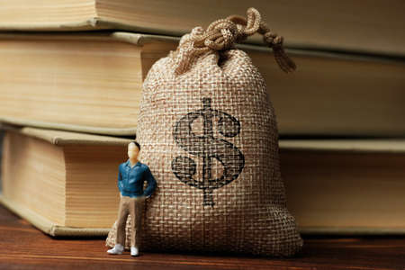 The concept of capital. The model of a man next to a bag of money against a background of books
