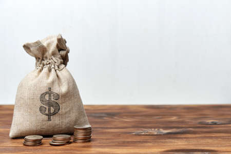 Bag of money and coins on a wooden table with a white background for copy space.