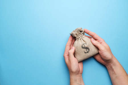 Savings concept. Hands holding a bag of money against a blue background with a copy space