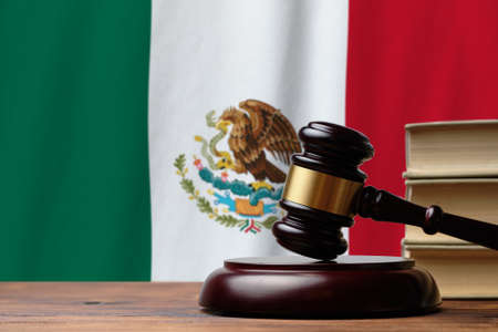 Justice and court concept in United Mexican States. Judge hammer on a Mexico flag background.
