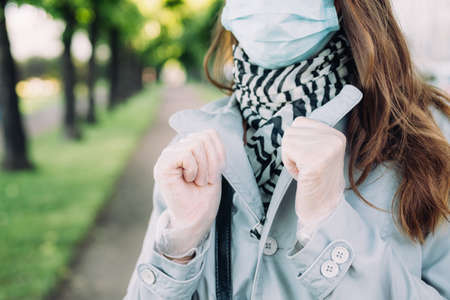 Caucasian girl in a medical mask and a gray coat walks in the park.