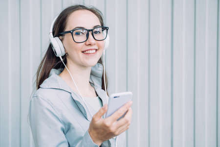Caucasian girl in headphones smiles and listens to music while walking around the city.