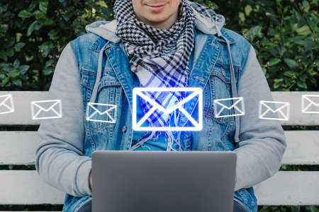 Caucasian man sits on a bench and scans email.