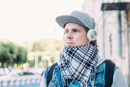 Caucasian man in headphones listens to music and walks around the city.