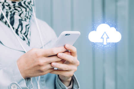 The concept of uploading data to the Internet cloud system. Girl holds a smartphone next to the icon