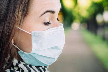 Portrait of a thirty-year-old Caucasian girl in a medical mask with closed eyes on a park background.