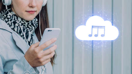 The concept of listening to music from the cloud on a smartphone. The girl is holding the phone Banque d'images