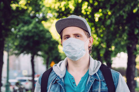 Caucasian man thirty years in medical mask walks through the park in summer. Banque d'images