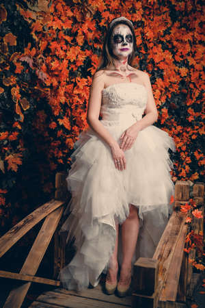 Woman with ghost make-up and wedding dress on yellow leaves background.