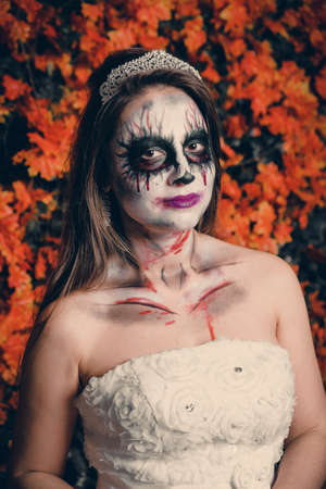 Portrait of a woman with ghost make-up and wedding dress.