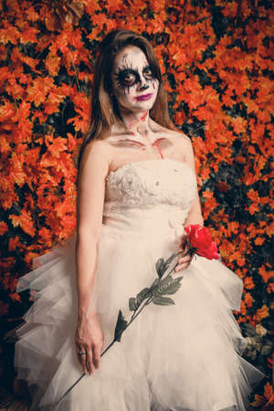 Woman with ghost make-up and wedding dress holding a rose.