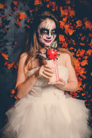 Portrait of woman with ghost make-up and wedding dress holding abstract bloody apple. Stockfoto