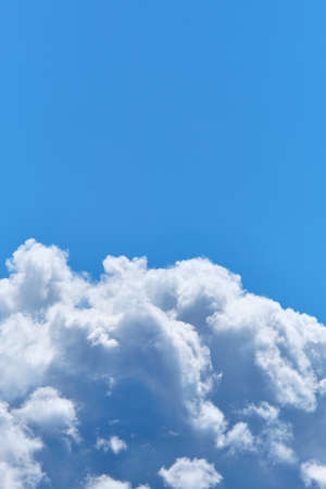 Thick clouds against the blue sky in the summer. Vertically.
