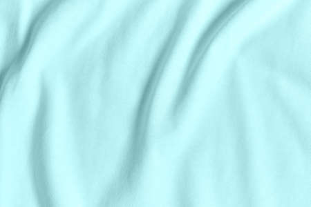Texture and background of crumpled pastel turquoise fabric.