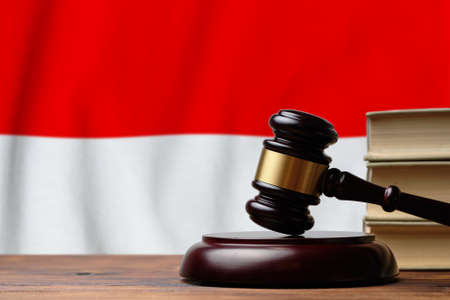 Justice and court concept in Republic of Indonesia. Judge hammer on a flag background.