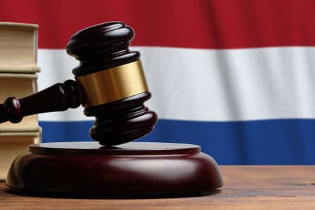 Justice and court concept in Netherlands. Judge hammer on a flag background.