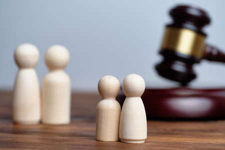 The concept of deprivation of parental rights through the court. Abstract children and parents next to the judge hammer.