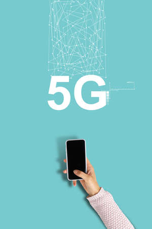 5G network inscription with hand holding smartphone. Stock fotó
