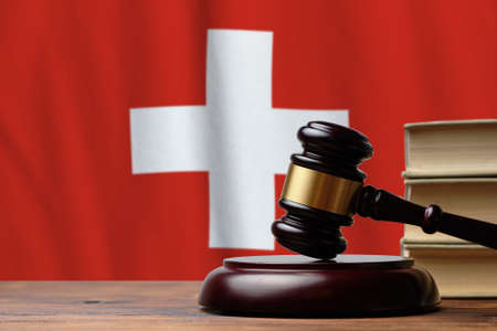 Justice and court concept in Swiss Confederation. Judge hammer on a Switzerland flag background.