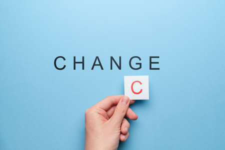 Chance and change concept. Hand with a white sticker on a blue background Foto de archivo