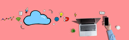 Internet Cloud Service Concept. Hand holds a smartphone on a pink background with laptop