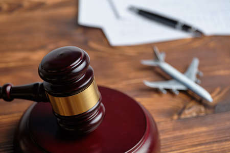 Concept of infringement of the rules of flying on an airplane next to the judge hammer.