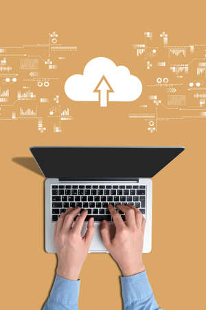 Cloud storage concept. Hands on a laptop with an orange background Stock fotó