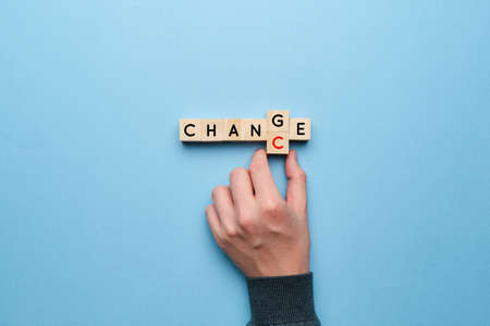 The concept of change and chance. Hand picks up letters on a yellow background Foto de archivo