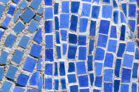 Wall of blue crushed mosaic tiles as background.