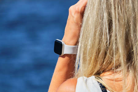 Smartwatch on the girl hand on the background of the sea.