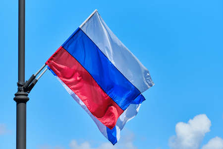 The Russian flag develops from the wind against the background of the sky.